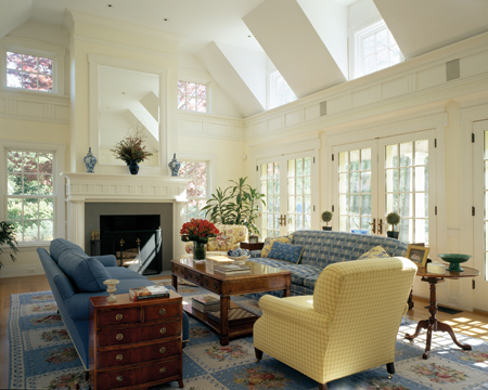 The one-and-a-half-story family room shares an open space with the kitchen. It features two levels of windows and French doors, as well as a Classically-detailed fireplace.