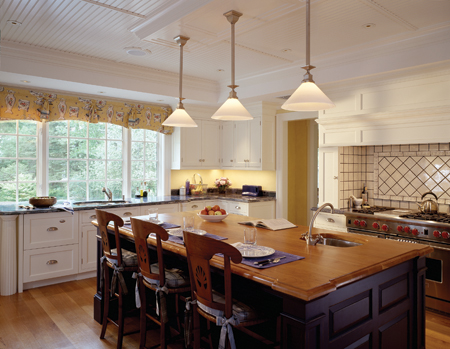 A marine-grade, finished-teak island anchors the kitchen. White oak floors unite the casual and formal spaces and complement the bead-board ceiling and Shaker-style cabinets.