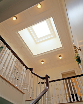 A skylight illuminates the second-floor central hall, around which the master suite, two bedrooms, a bathroom, an additional bedroom suite and a laundry area are organized.