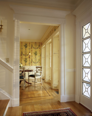 As viewed from the main entry, the dining room contains Greek Revival details such as crown molding, wainscoting and window casings with operable angled shutters. The door surround supports an Egyptian-inspired over-scaled crown.