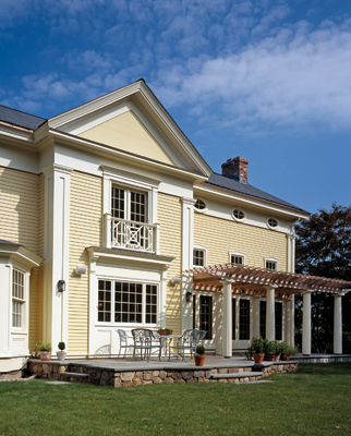 The rear elevation is detailed to match the front facade, but features a centered main gable, pergola and three sets of French doors that lead to a bluestone terrace.