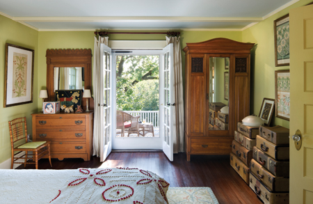 By removing a wall and centering the door, Brewer created a large bedroom with windows on three sides, and French doors that open to the balcony above the entry porch. Photo: © Francis Dzikowski / Esto