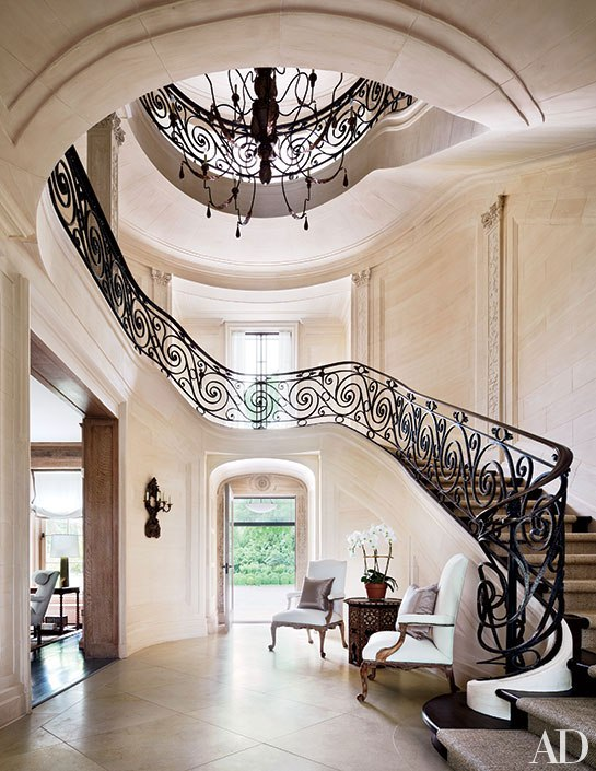 At a Water Mill, New York, home, a wrought-iron balustrade wraps the serpentine staircase in the entrance hall. Photo: Scott Frances